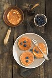 Pancakes with blueberries. And a small pan royalty free stock image