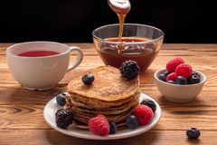 Pancakes with blueberries and strawberries and cup of red juice with cup of honey. Soft focus. Pancakes with blueberries and strawberries and cup of red juice royalty free stock photos
