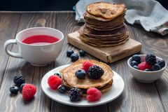 Pancakes with blueberries and strawberries and cup of red juice. View of pancakes with blueberries and strawberries and cup of red juice stock photography