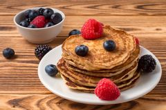 Pancakes with blueberries and strawberries and cup of red juice on wooden background. Close Up. Soft focus. Pancakes with blueberries and strawberries and cup of royalty free stock photography