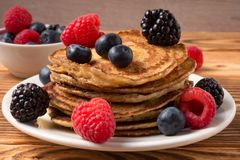 Pancakes with blueberries and strawberries and cup of red juice on wooden background. Close Up. Soft focus. Pancakes with blueberries and strawberries and cup of stock images