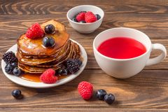 Pancakes with blueberries and strawberries and cup of red juice on wooden background. View of Pancakes with blueberries and strawberries and cup of red juice on stock photos