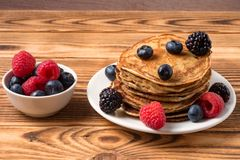 Pancakes with blueberries and strawberries and cup of red juice on wooden background. View of Pancakes with blueberries and strawberries and cup of red juice on stock images