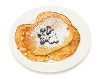 Pancakes with blueberries on white background. Tasty golden pancakes with blueberries sprinkled with confectionery sugar, isolated on white Royalty Free Stock Photography