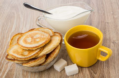 Pancakes in bowl, sour cream, tea and lumpy sugar. Pancakes in bowl, jug of sour cream, tea and lumpy sugar on wooden table Royalty Free Stock Photos