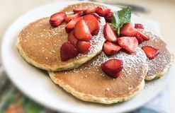 Pancakes breakfast with strawberries and mint inside restaurant. royalty free stock photo