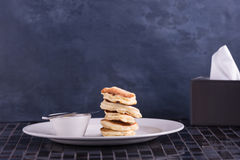 Pancakes with butter on dish Royalty Free Stock Photos