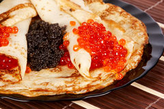 Pancakes with caviar. Pancakes with red and black caviar on a plate Royalty Free Stock Photo