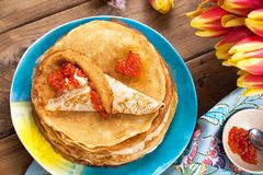 Pancakes with caviar and butter, a bouquet of fresh tulips and a wooden background. Traditional Russian food for carnival. Top royalty free stock photo