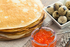 Pancakes with caviar and quail eggs Stock Photos
