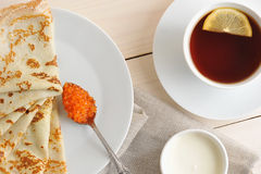 Pancakes with caviar and sour cream on a saucer Stock Photography