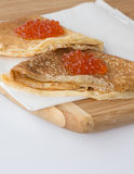 Pancakes with caviar. On wooden desk on white backgoround Royalty Free Stock Photo