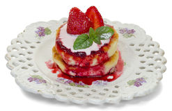 Pancakes with cheese. Pancakes with curd cheese with syrup and strawberries on an old ceramic plate isolated on white background Royalty Free Stock Images