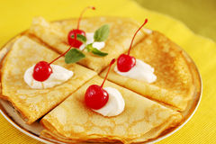 Pancakes and cherries Stock Images