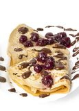 Pancakes with cherry jam and chocolate icing Stock Images