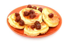 Pancakes with cherry jam on the red plate Stock Photos