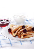 Pancakes with cherry jam and with sour cream Stock Photo