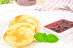Pancakes with cherry jam in square  plate on the wooden table Royalty Free Stock Photography