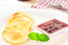 Pancakes with cherry jam in square  plate on the wooden table Stock Photography