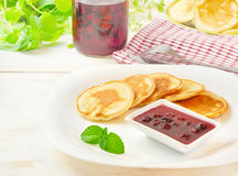 Pancakes with cherry jam in square  plate on the wooden table Royalty Free Stock Photo
