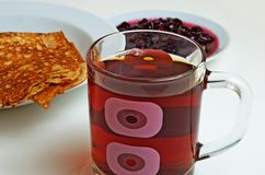 Pancakes and cherry jam with tea for breakfast. Royalty Free Stock Photos