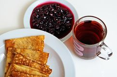 Pancakes and cherry jam with tea for breakfast. Royalty Free Stock Photography