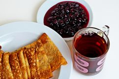 Pancakes and cherry jam with tea for breakfast. Royalty Free Stock Image
