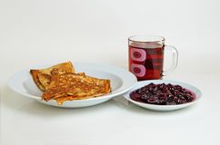Pancakes and cherry jam with tea for breakfast. Stock Photo