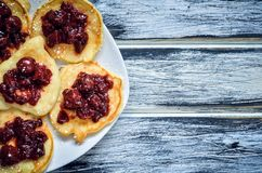 Delicious sweet meal. Pancakes with cherry jam on a wooden table royalty free stock photos
