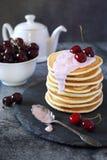 Pancakes with cherry yoghurt and fresh cherries. On the dark background Royalty Free Stock Photo