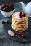 Pancakes with cherry yoghurt and fresh cherries. On the dark background Royalty Free Stock Images