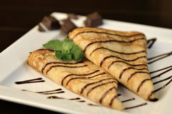 Pancakes with chocolate sauce. Russian pancakes with chocolate sauce, chocolates and mint royalty free stock photography