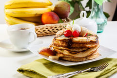Pancakes with chocolate sauce fruit and coffee. American pancakes with chocolate sauce fruit and coffee Stock Photography