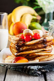 Pancakes with chocolate sauce fruit and glass of milk. American pancakes with chocolate sauce fruit and glass of milk Stock Photo