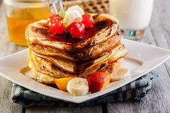 Pancakes with chocolate sauce fruit and glass of milk Royalty Free Stock Photography