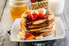 Pancakes with chocolate sauce fruit and glass of milk. American pancakes with chocolate sauce fruit and glass of milk Royalty Free Stock Photos