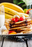 Pancakes with chocolate sauce fruit and glass of milk Stock Photo
