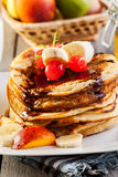 Pancakes with chocolate sauce fruit and glass of milk. American pancakes with chocolate sauce fruit and glass of milk Royalty Free Stock Images