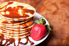 Pancakes with chocolate souce. Pancakes stak topped with chocolate souce on wooden table, pancakes in left side, horizontal picture stock photo