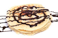 Pancakes with chocolate syrup. Some pancakes with chocolate syrup on a white background Stock Photo