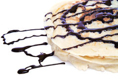 Pancakes with chocolate syrup. Some pancakes with chocolate syrup on a white background stock photos