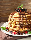 Pancakes with chocolate syrup and berrie fruits. Sweet tasty pancakes with berrie fruits, chocolate syrup and mint leaves royalty free stock images
