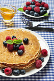 Pancakes close up. Delicious pancakes close up, with fresh blueberries, raspberry and maple syrup Royalty Free Stock Images