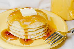 Pancakes and Coffee. Stack of pancakes with butter, maple syrup, and fork.  Coffee in background Royalty Free Stock Images
