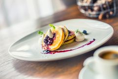 Pancakes and coffee. Pancakes with a cup of coffee and fresh fruits blueberries and herb decoration. Stock Photos