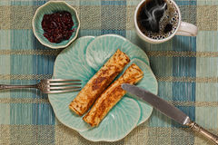 Pancakes and coffee - horizontal top view. Breakfast of two pancakes, jam and coffee in original crockery top view royalty free stock image