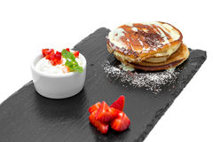 Pancakes with condensed milk. And strawberry on a black board royalty free stock image