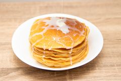 Pancakes with condensed milk on a white light background. A stack of pancakes with sweet sauce. Close up view. stock images