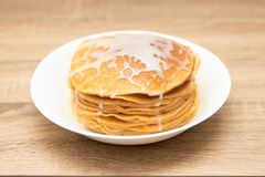 Pancakes with condensed milk on a white light background. A stack of pancakes with sweet sauce. Close up view. stock image