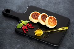 Pancakes with cottage cheese, berries and honey. On a black concrete background Stock Images